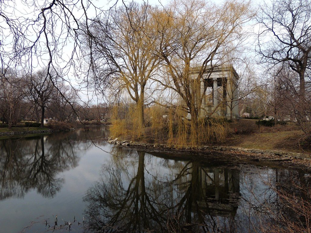 photo shows a peaceful pond in graceland cemetery on an autumn day